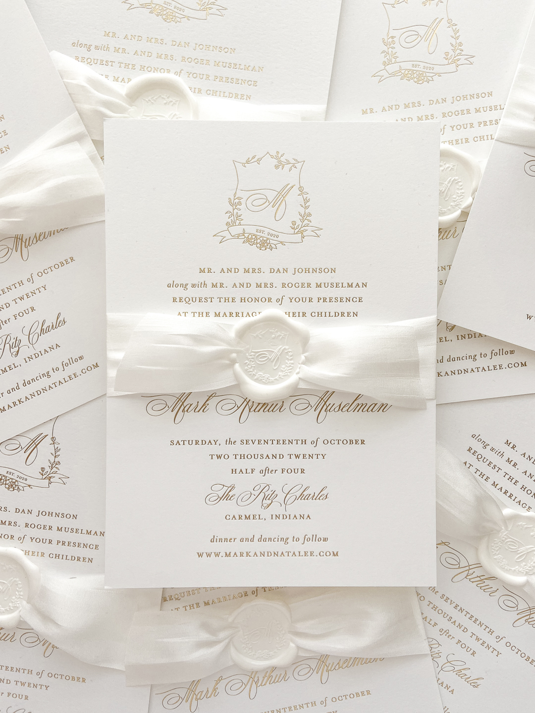Gold foil wedding invitation with floral crest and monogram wrapped in white silk ribbon and white wax seal.