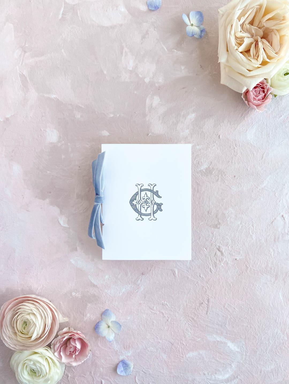 Booklet ceremony program with vintage monogram cover and dusty blue velvet ribbon.