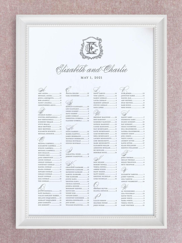 Wedding seating chart with floral crest and interlocking monogram organized alphabetically.