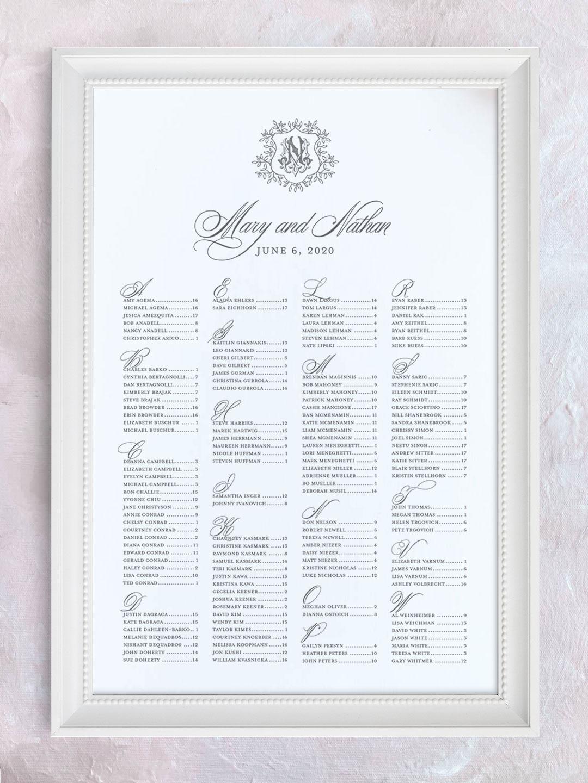 Wedding seating chart with greenery crest and interlocking monogram organized alphabetically.