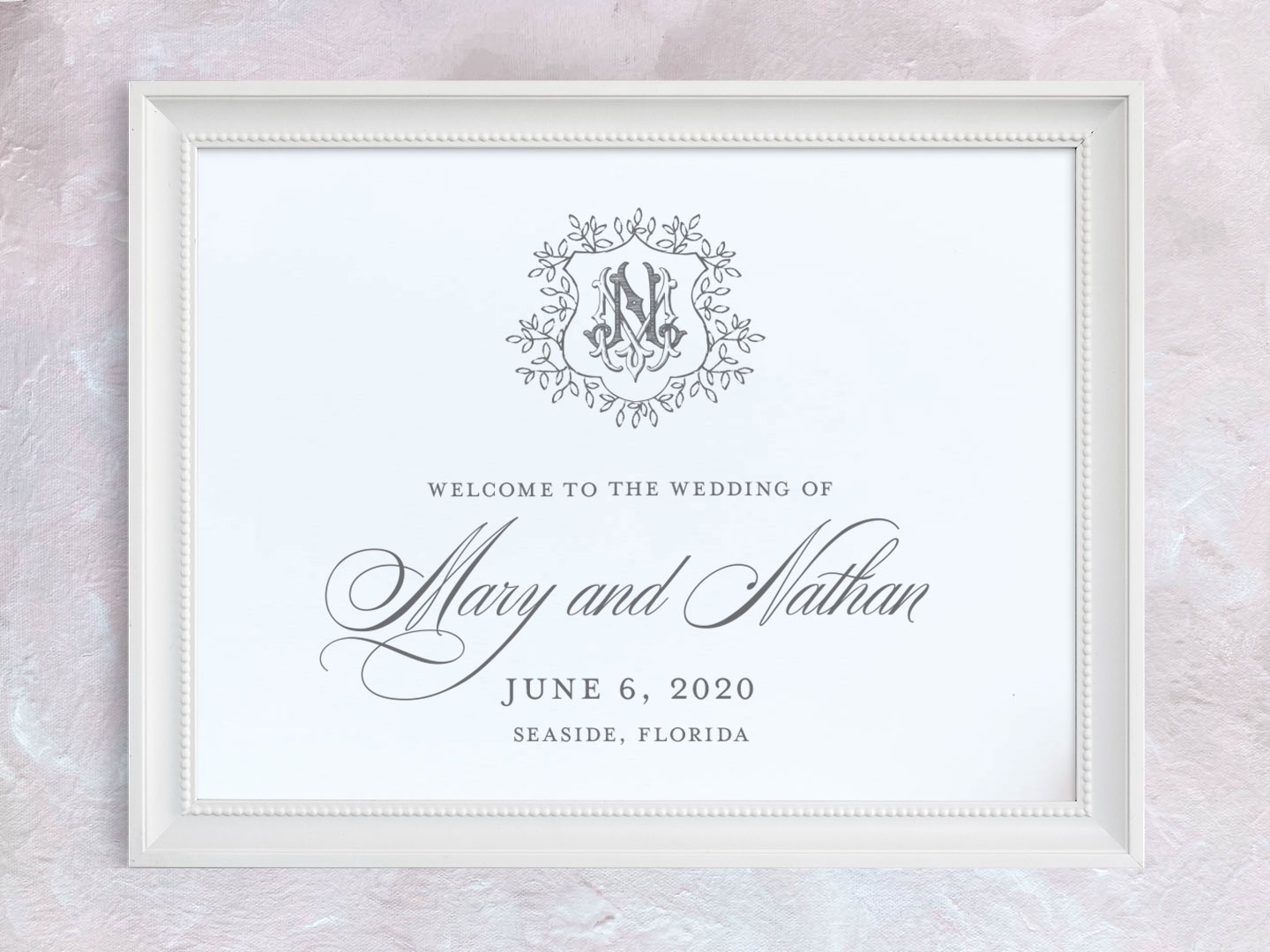 Wedding welcome sign with greenery crest and vintage monogram.