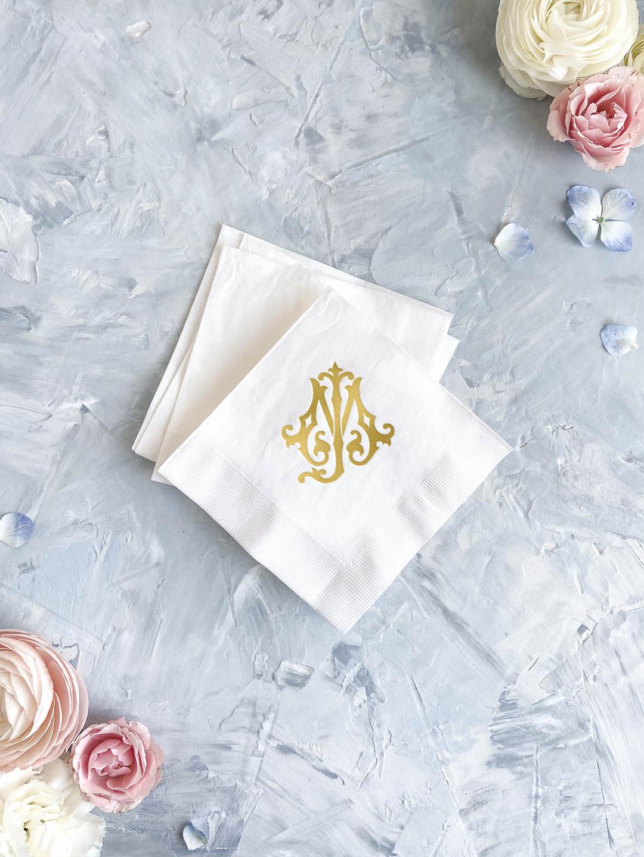 Gold foil stamped wedding cocktail napkins. Interlocking monogram design on white napkin.