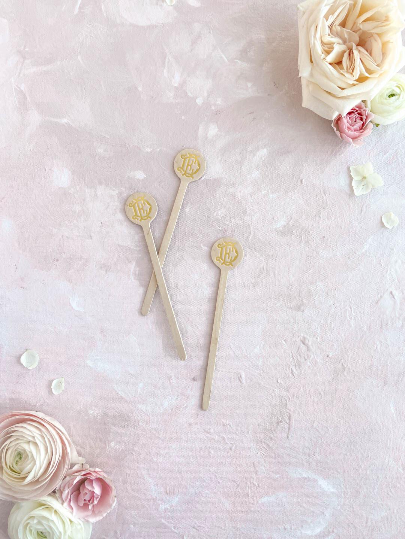 Gold foil stamped wooden wedding stir sticks. Interlocking monogram design.