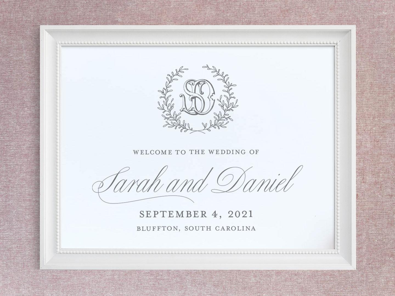 Wedding welcome sign with greenery wreath and interlocking monogram.